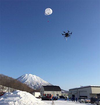 雪山での遭難者位置特定、ドローンと気球で実現